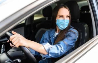 Autonoleggio, donna con mascherina in un'auto sanificata da società di noleggio a lungo termine