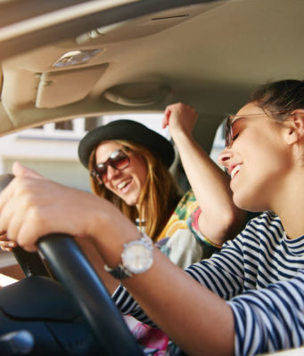 City car, due ragazze felici a bordo di una citycar a noleggio lungo termine
