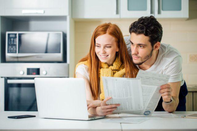 Coppia felice legge una bolletta dopo aver effettuato voltura e cambio fornitore
