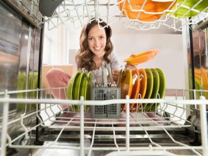 Lavastoviglie consuma sale, donna felice inquadrata dall'interno della lavastoviglie